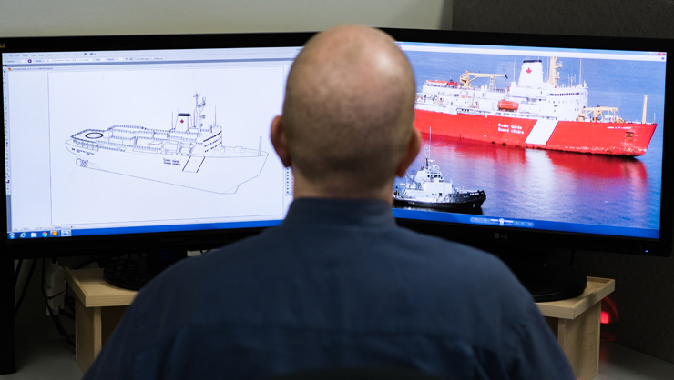 computer monitors showing naval rendering of a ship and the finished ship on the water